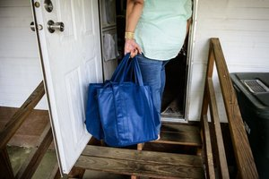 Joann Bellamy carries a weeks worth of meals to Blanche  Johnson's home in West Fayetteville.